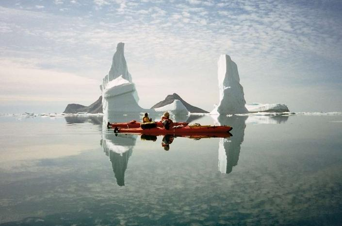 Two people kayaking next to large icebergs in crystal clear water. Photo by Arctic Dream, Visit Greenland