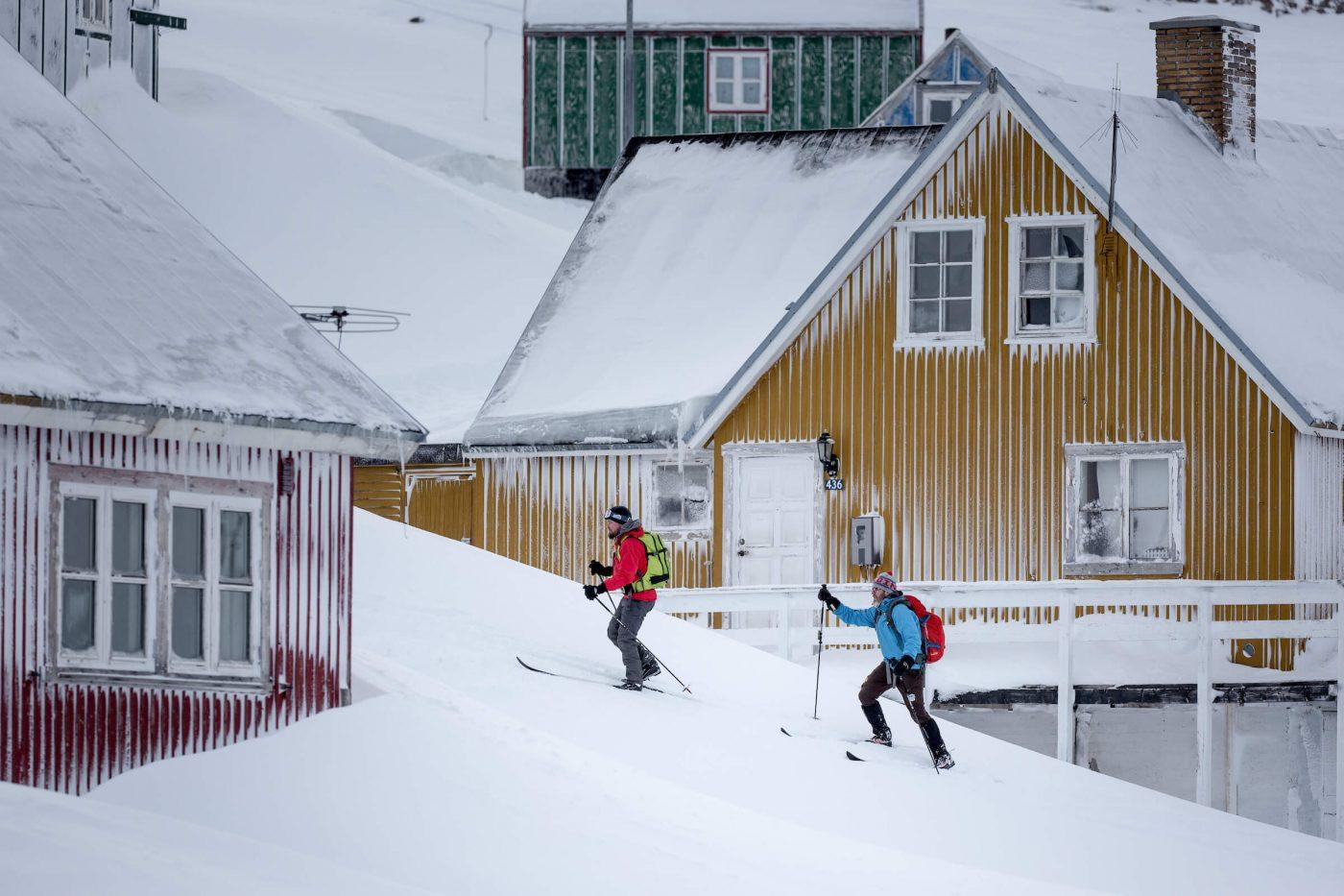Two cross country skiers ascending between houses in Tasiilaq in East Greenland
