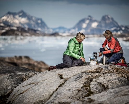 Two hikers at a camp in East Greenland preparing dinner. By Mads Pihl