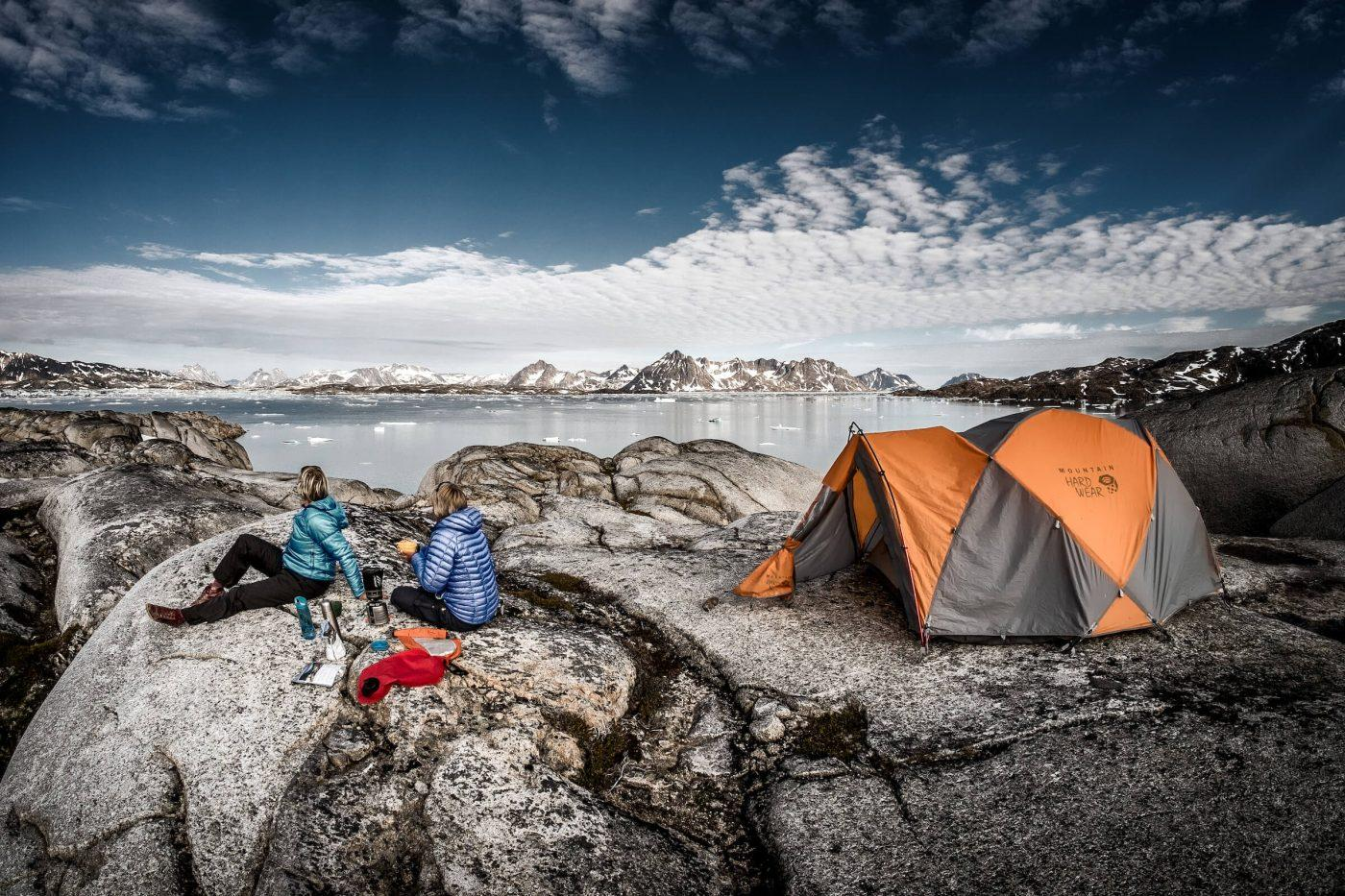 Two hikers enjoying the view from Qernertivartivit over Ammassalik Fjord in East Greenland. By Mads Pihl