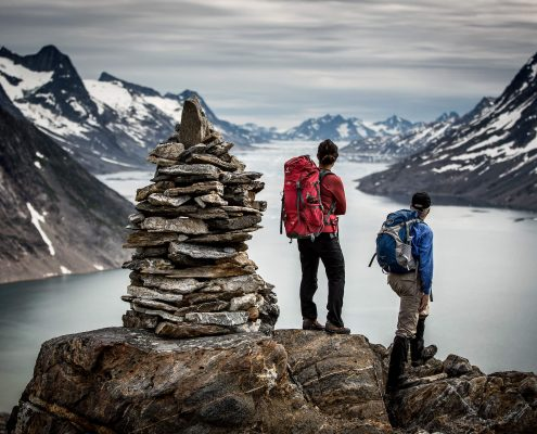 Two hikers on a Greenland Travel trek looking out over Ikaasatsivaq sound in East Greenland near Tiniteqilaaq. By Mads Pihl
