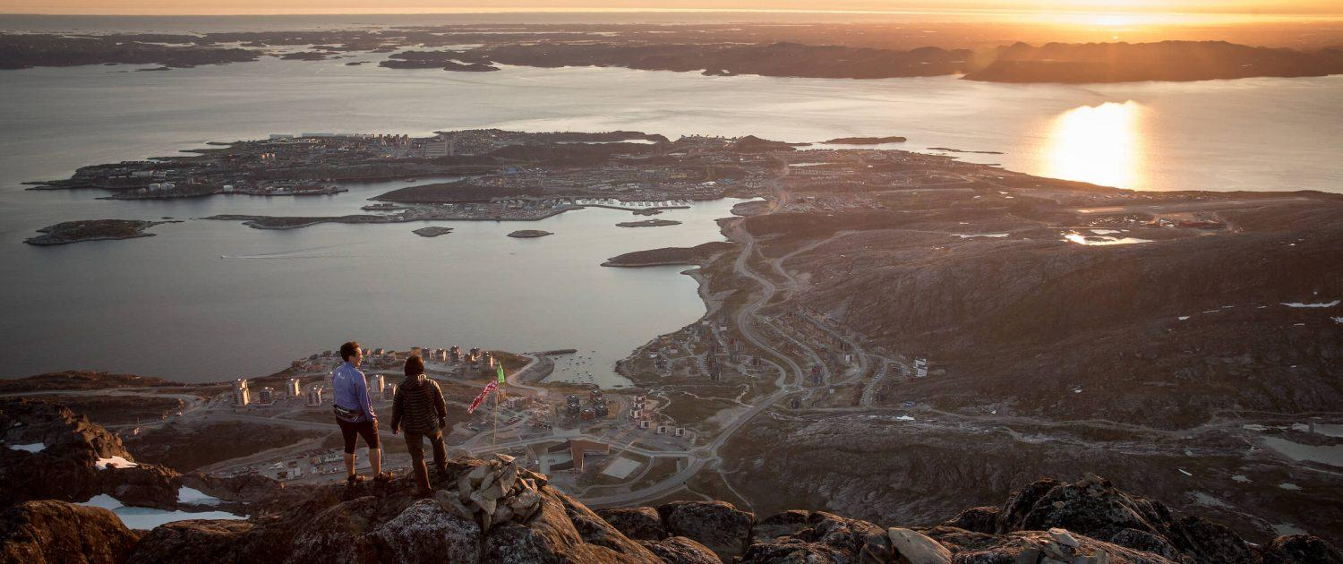 Two hikers overlooking Nuuk in the midnight sun from the peak of Ukkusissaq - Store Malene in Greenland. By Mads Pihl
