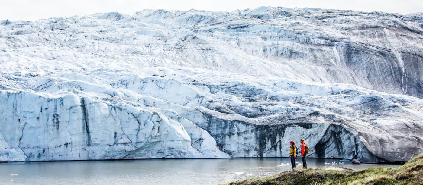 Two hikers reach the Russell Glacier, part of the Greenland Ice Sheet, in the Kangerlussuaq backcountry. By Raven Eye Photography