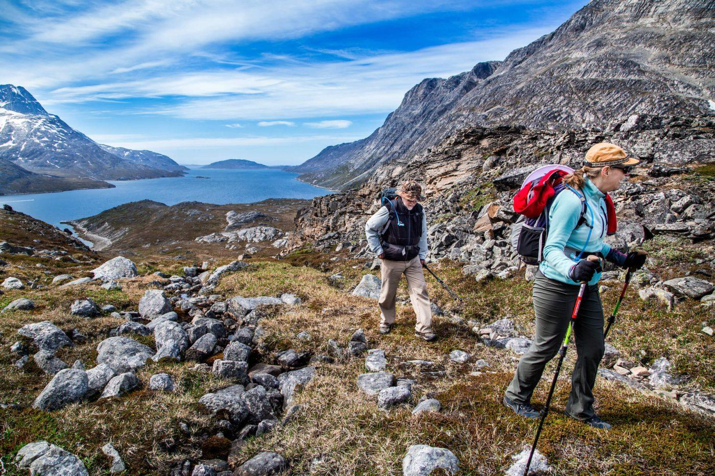 Two mature travelers hiking in the Nuuk backcountry with Touring Greenland crossing from the bottom of Kobbefjord over to Nuuk Fjord. Photo by Raven Eye Photography