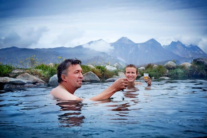 Two people enjoying a cold drink at Uunartoq hot springs in South Greenland, by Camilla Hey