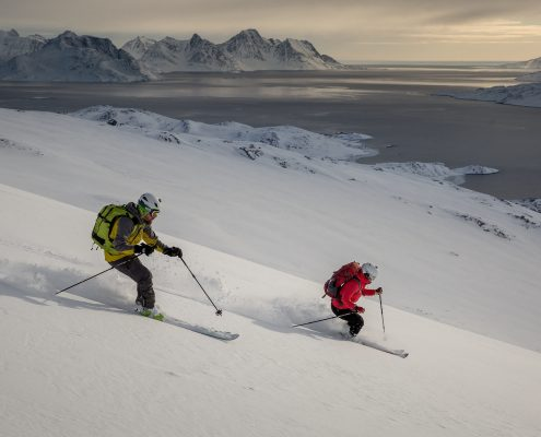 Two skiers in the sunset descending towards the fjord near Kuummiut in East Greenland. By Mads Pihl