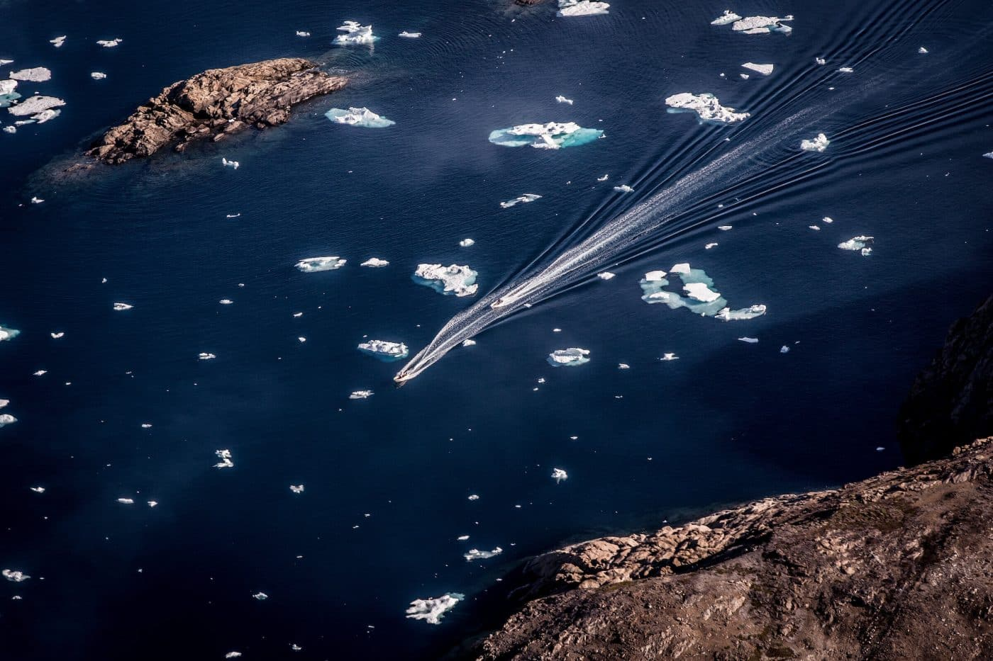 Two small boats along the coastline in East Greenland near Tasiilaq. By Mads Pihl