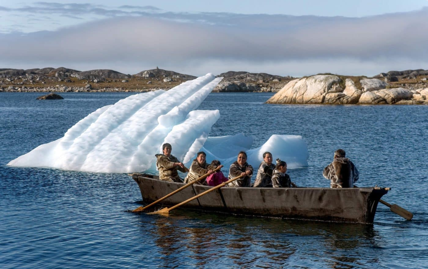 Umiaq with greenlanders in seal skin costumes, by John Rasmussen