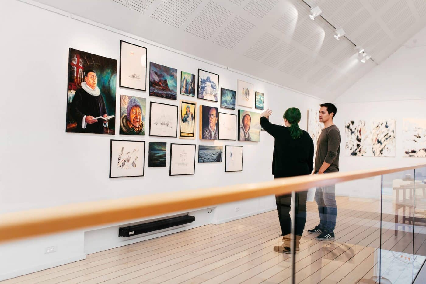 Visitors of Nuuk Art Museum talking about and looking at art from the Kimik exhibition. By Rebecca Gustafsson