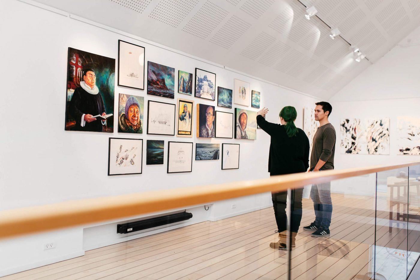 Visitors of Nuuk Art Museum talking about and looking at art from the Kimik exhibition. Photo by Rebecca Gustafsson
