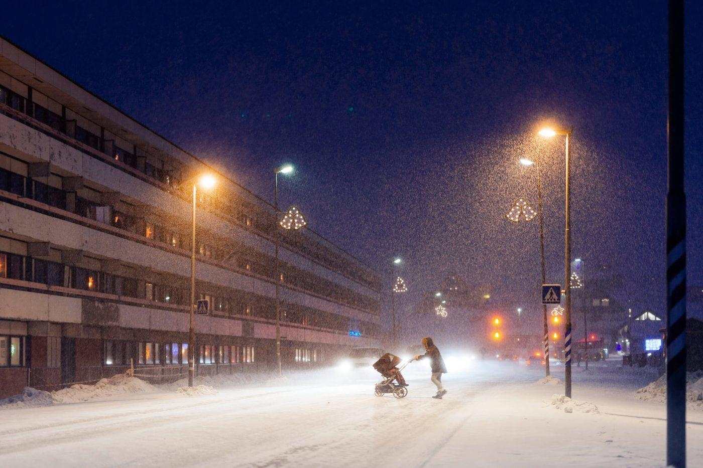 Woman crossing the road with a stroller on a snowy december afternoon in Nuuk in Greenland. Photo by Rebecca Gustafsson