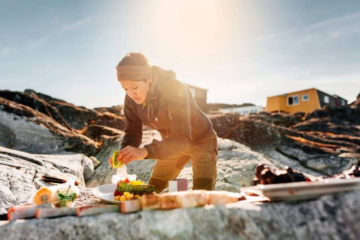 Woman preparing greenladic specialties on the rocks on the beach by Inuk Hostels in Nuuk in Greenland. By Rebecca Gustafsson