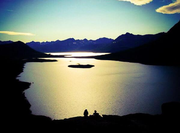 Two people looking over the Tasermiut Fjord. Visit Greenland