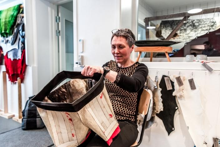 Woman at Kittat workshop in Nuuk working on a pair of sealskin shorts as part of the Greenland National Costume, called Kalaallisuut. Photo by Lola Akinmade Akerstrom - Visit Greenland