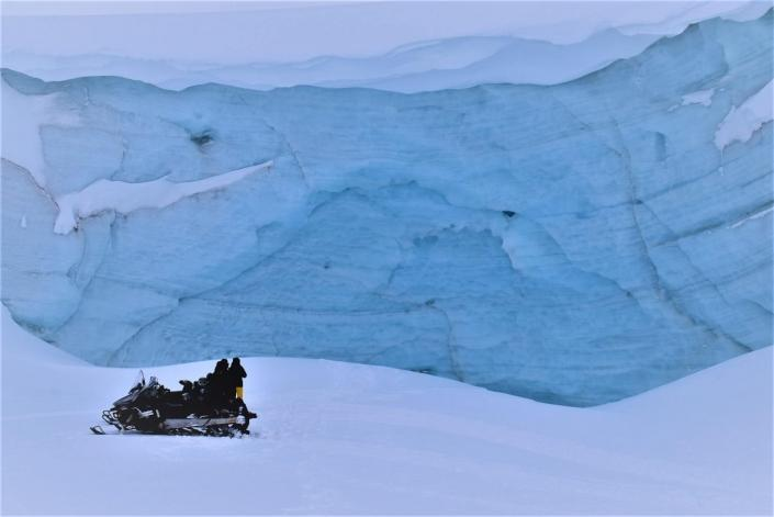 Photobreak on a snowmobile in front of glestcher in East Greenland. Photo by Tasiilaq Tours - Visit Greenland