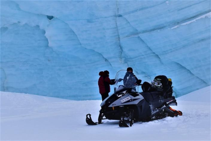 Two people in front of a gletscher on snowmobile in East Greenland. Photo by Tasiilaq Tours