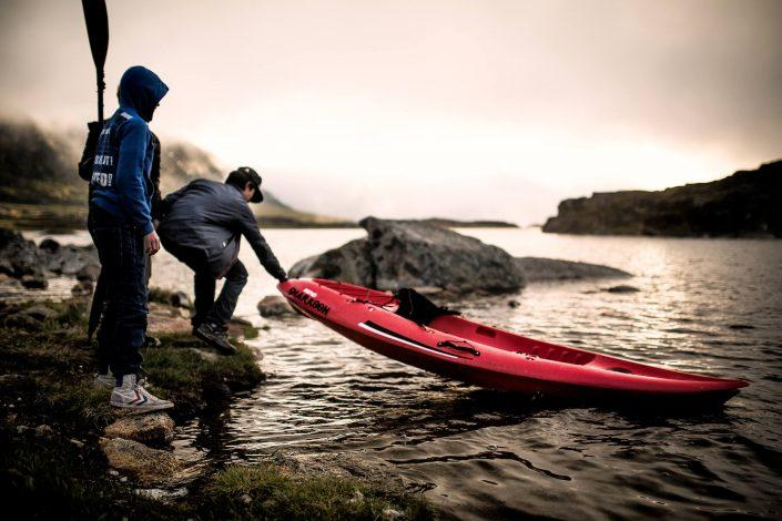 Boys from Qaqortoq in South Greenland launching a small kayak in the lake Tasersuaq just behind town. Photo by Mads Pihl.