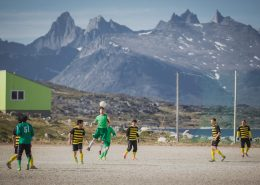 A game of soccer in Nanortalik in South Greenland with a backdrop of rugged peaks. Photo by Mads Pihl, Visit Greenland