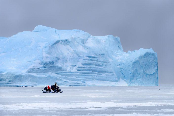 A snowmobile on the sea ice near a big iceberg in the Uummannaq area of North Greenland. Photo by Marcela Cardenas.