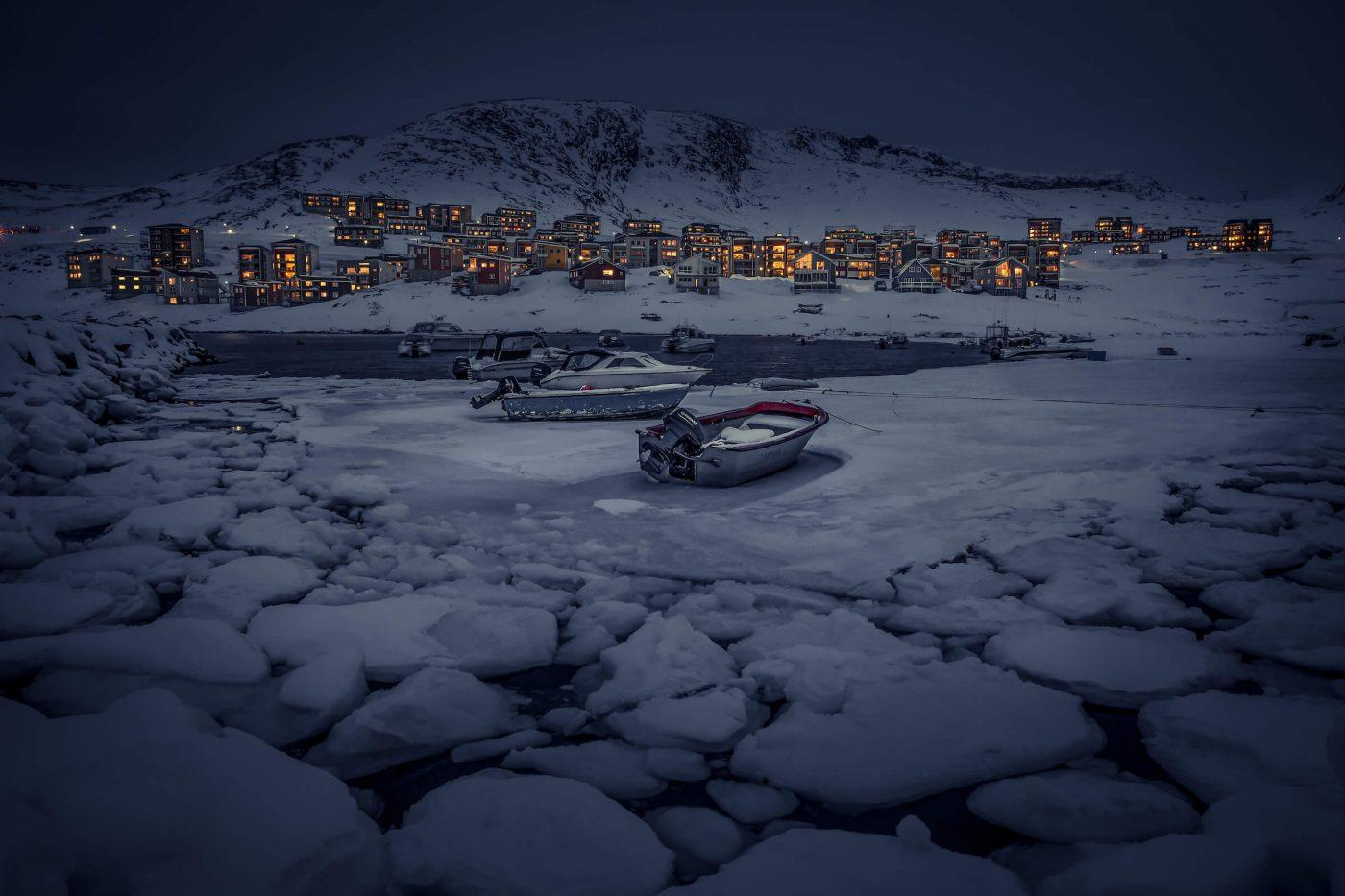 A winter evening scene from Qinngorput harbour in Nuuk in Greenland. By Mads Pihl