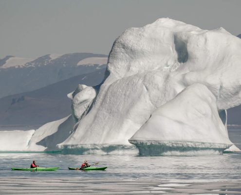 Kayakers near an iceberg in Illorsuit in North Greenland. Photo by Mads Pihl.