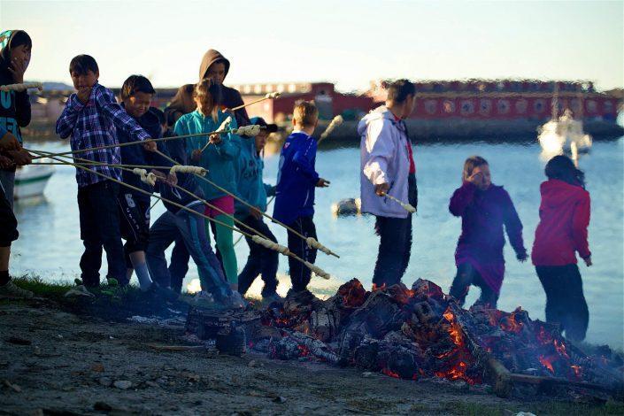 Kids making twist bread at bonfire in Aasiaat. Photo by Magssannguaq Qujaukitsoq.