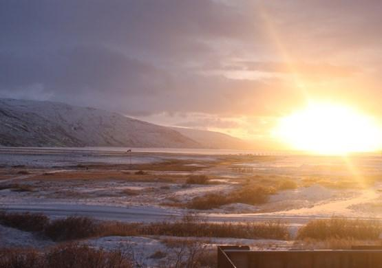 Sun illuminating snowy landscape. By Visit Greenland