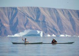 Two boys in Inuit kayaks, Qaanaaq. Photo by Glenn Mattsing.