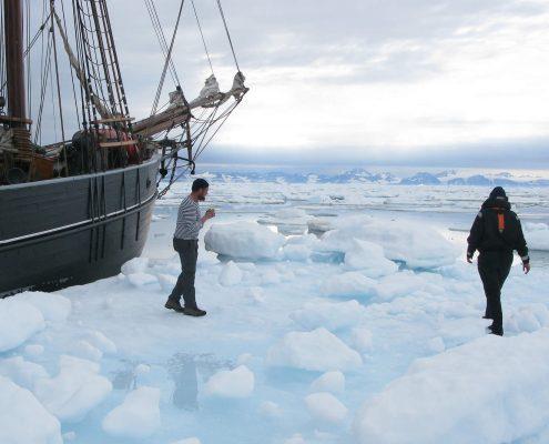Two people walking on ice floes in kangertittivaq fjord. Photo by Per Arnesen.