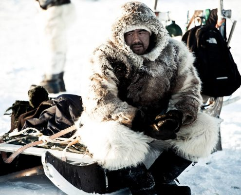 Man sitting on a sled in North Greenland. By André Shoenherr