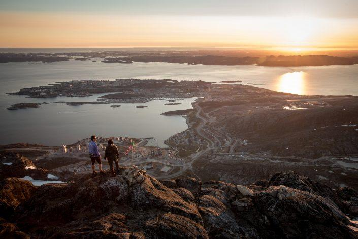 Two hikers overlooking Nuuk in the midnight sun from the peak of Ukkusissaq Store Malene in Greenland. By Mads Pihl
