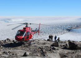 Tourists standing next to a helicopter while looking at the Greenland Ice Sheet. Photo by Arctic Nomad