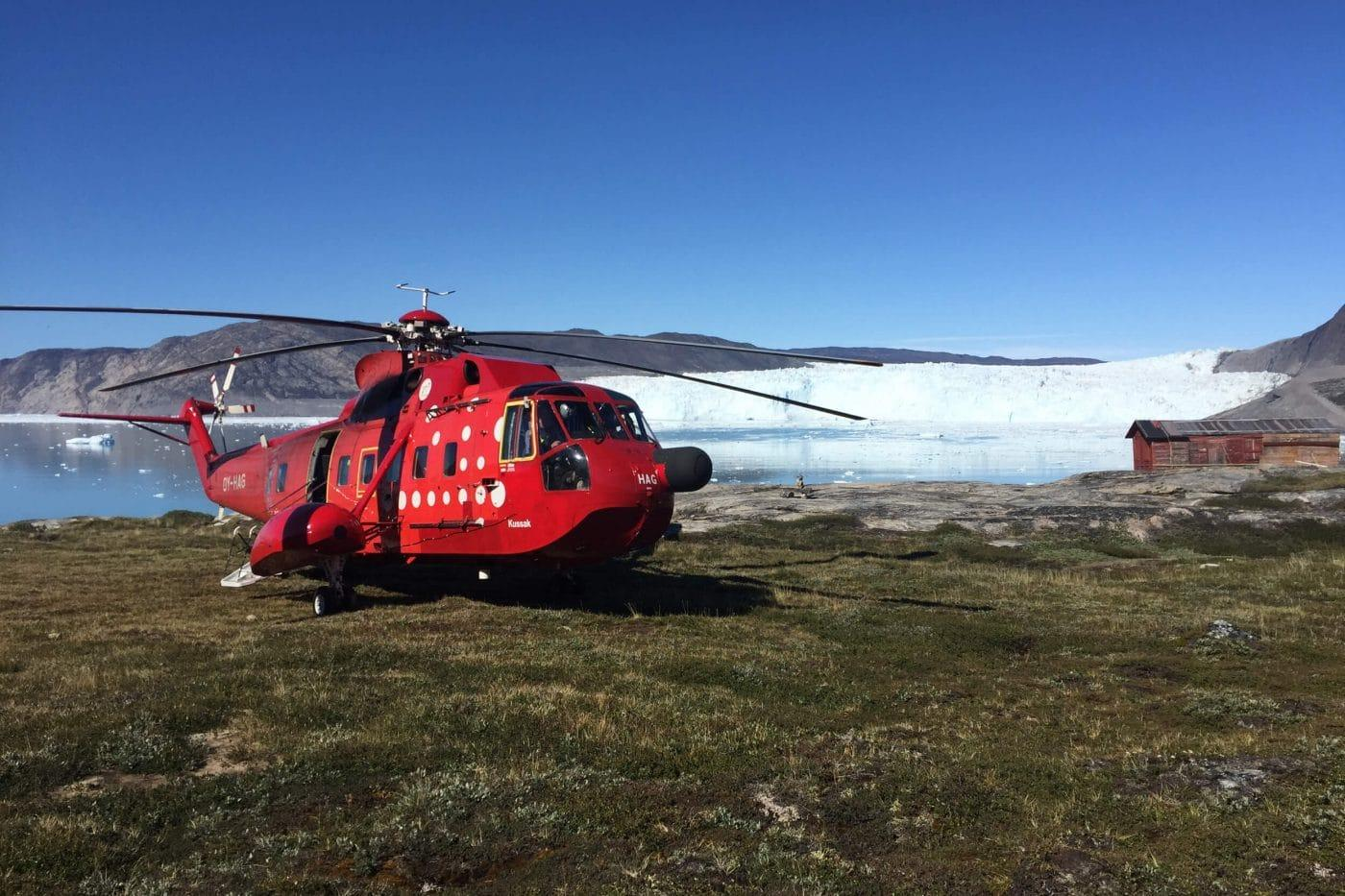 Red helicopter about to take off close to the water. Photo by Arctic Nomad, Visit Greenland