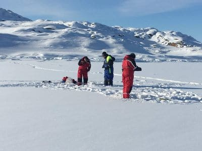 Local guide and tourists ice fishing. Photo by Ilulissat Water Safari