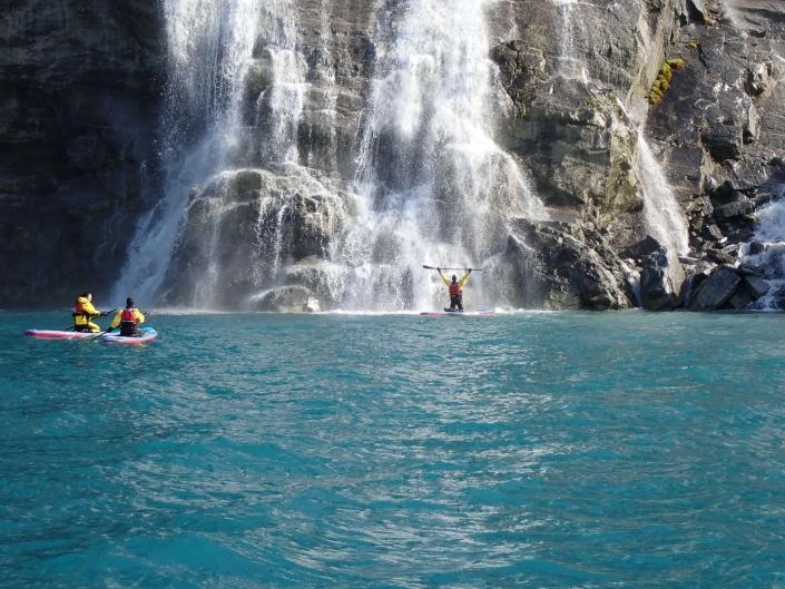 Three people near waterfall stand up paddleboarding. Photo by Nuuk Adventure - Visit Greenland