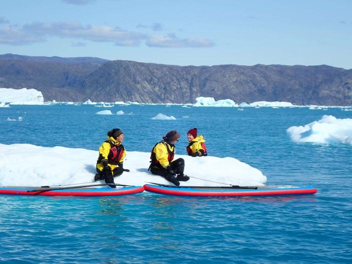 Women taking a break from stand up paddleboarding on an iceberg. Photo by Nuuk Adventure - Visit Greenland