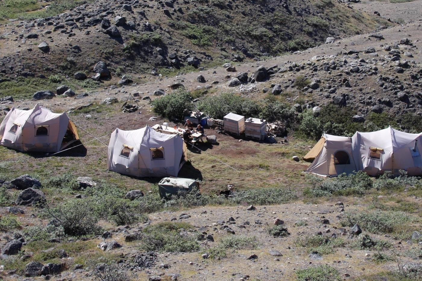 Summer camp in Kangerlussuaq with tents two people sitting at table eating. Photo by North Safari Travel