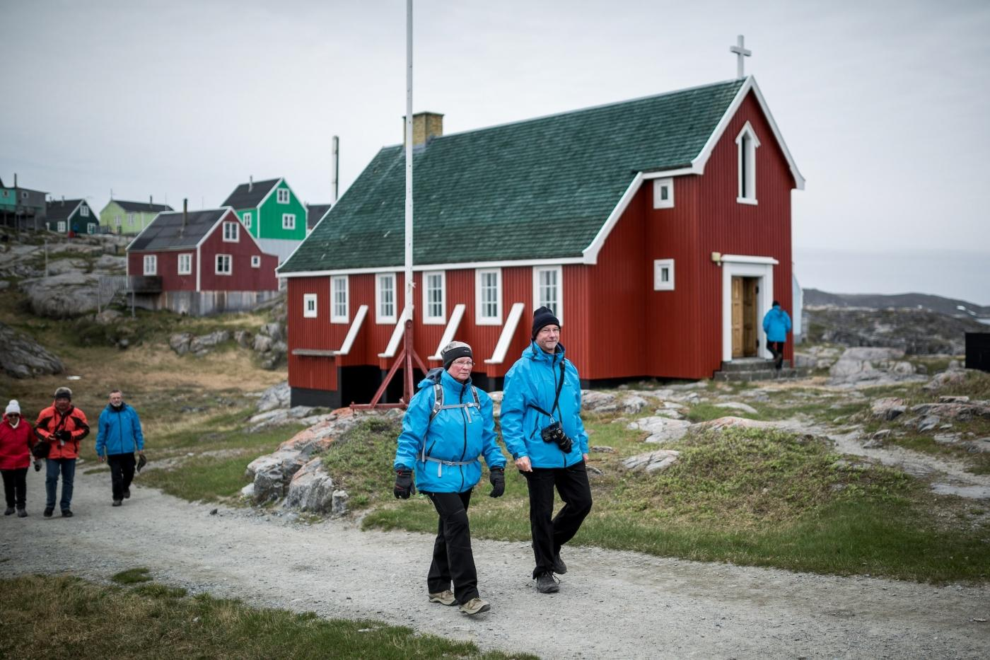 MS Fram cruise guests walking by the church in Itilleq in Greenland. Photo by Mads Pihl - Visit Greenland