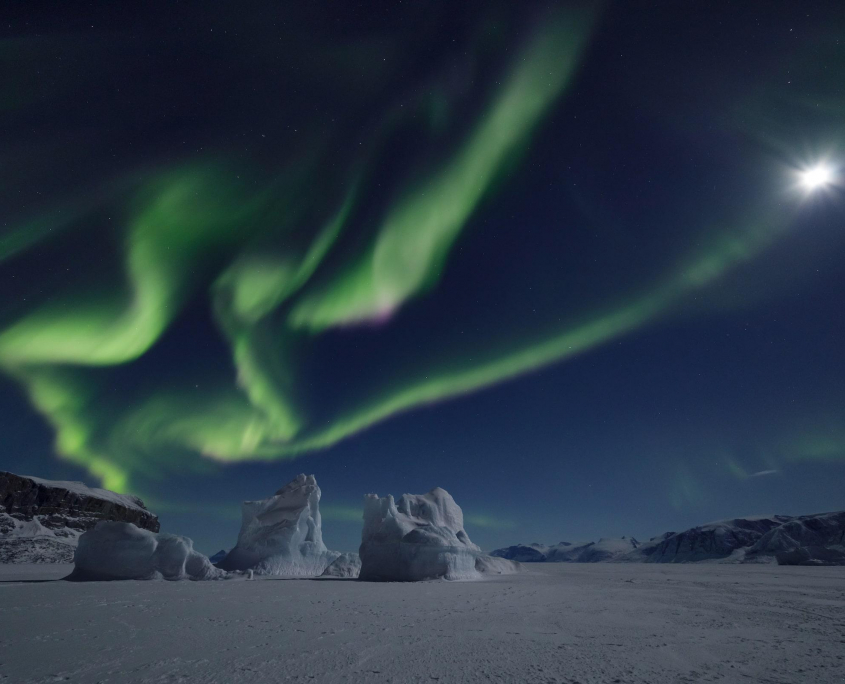 The northern lights and moon above the Uummannaq sea ice. Photo by Erez Marom - Visit Greenland