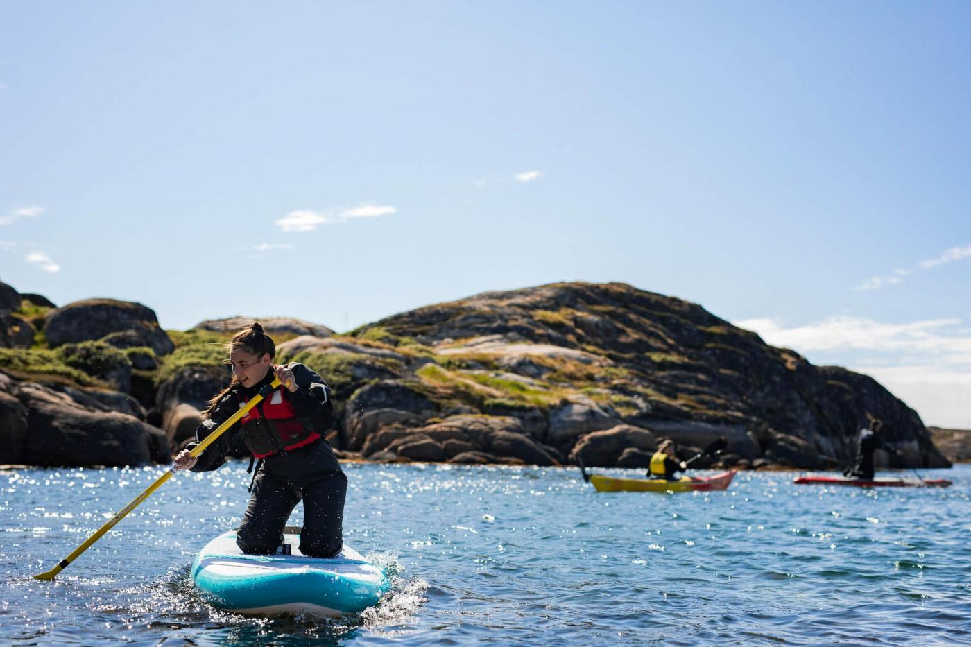 SUP and kayakers in Sisimiut. Photo - Aningaaq R. Carlsen, Visit Greenland