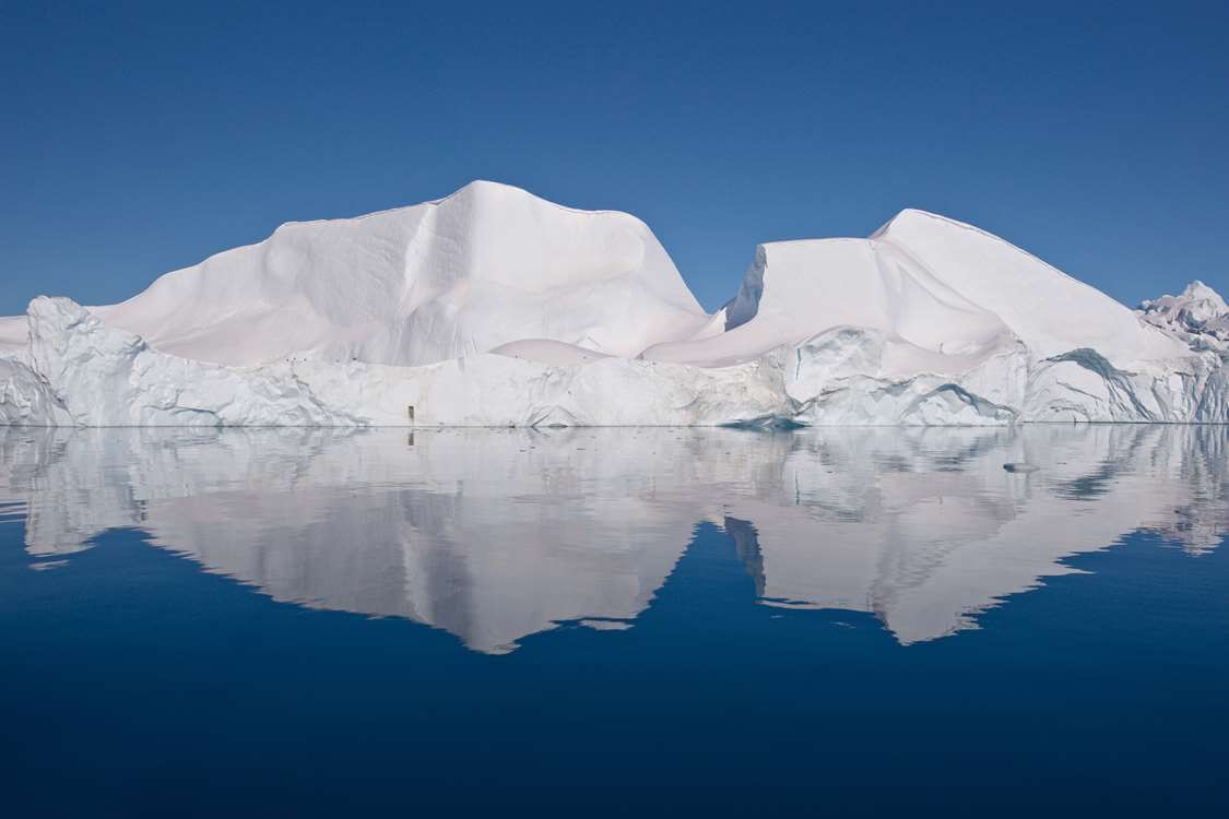 Large iceberg under clear blue skies. Photo by Thomas Eltorp, Visit Greenland