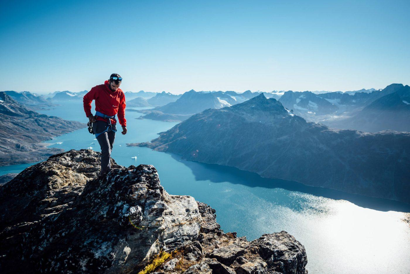 A climber walks a summit ridge, looking South down two fjords, West Of Tasiilaq Fjord. By Chris Brinlee Jr