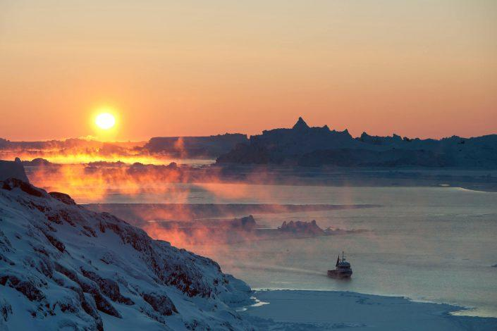 A fishing vessel approaching Ilulissat on a cold winter day in Greenland. Photo by Andre Schoenherr