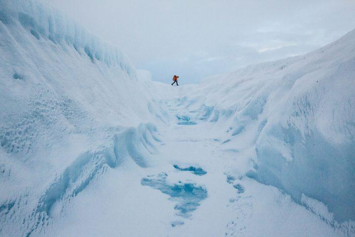 A glacier walking adventure by a crevasse on the Greenland Ice Sheet near Kangerlussuaq. Photo by Paul Zizka.