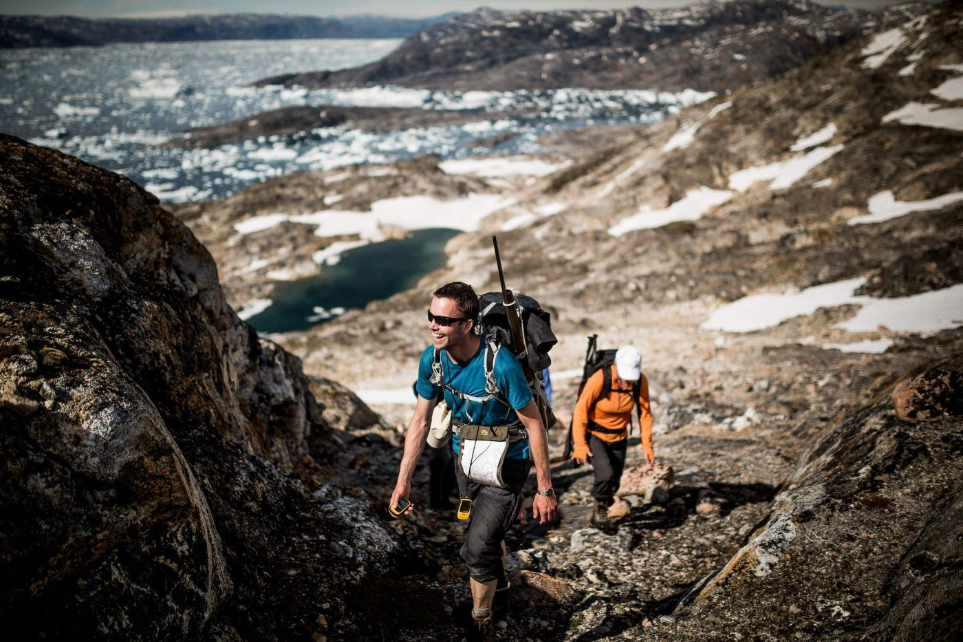 A Greenland Travel guide in East Greenland climbing a mountain in high spirits near Tiniteqilaaq. By Mads Pihl