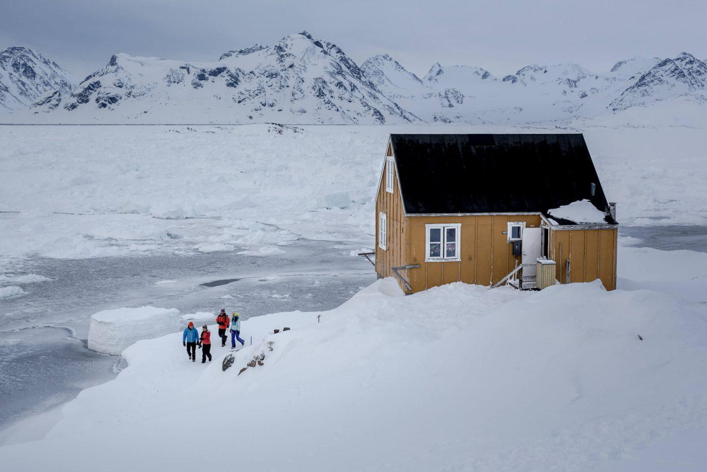 A group of travelers on a walk in Kulusuk in East Greenland. Photo by Mads Pihl