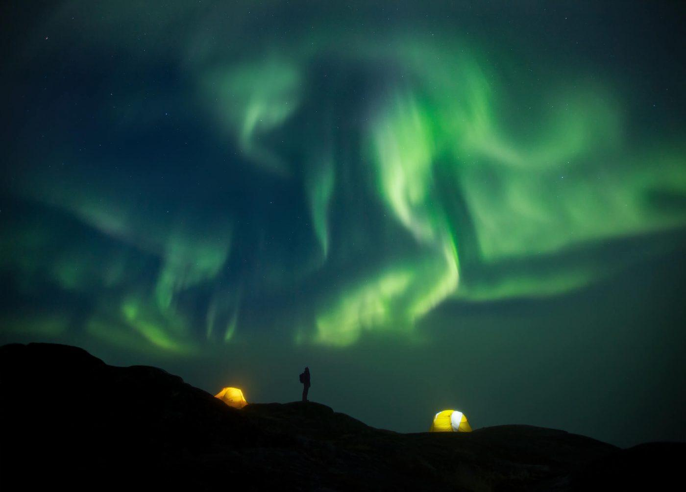 A happy backpacker stands outside her tent in her backcountry camp to watch the northern lights swirl over the Ilulissat Icefjord just beyond the hill. By Paul Zizka