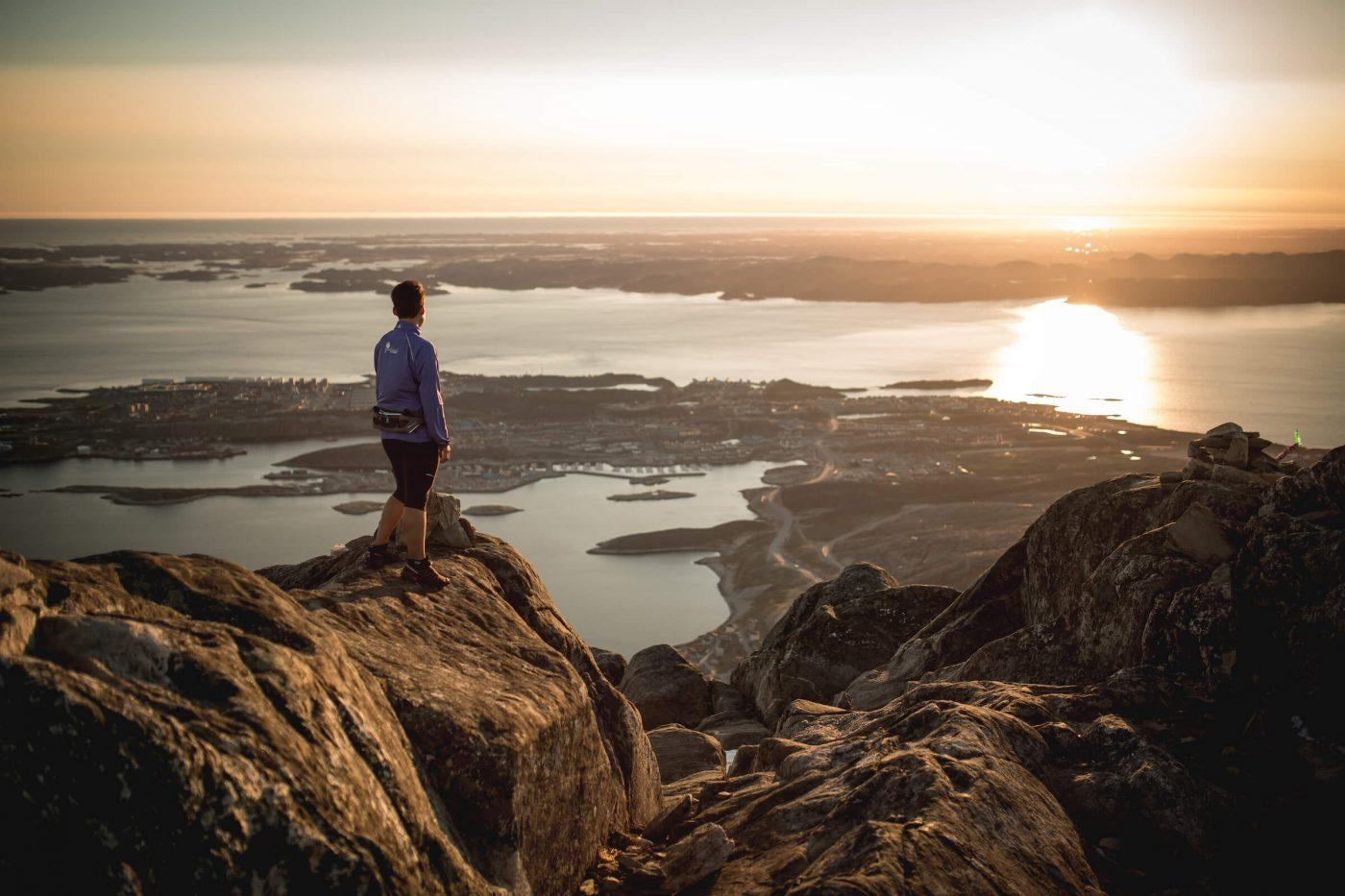A hiker enjoying the midnight sun and the view over Nuuk from the peak of Ukkusissaq - Store Malene in Greenland