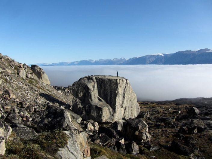 A hiker on a large rock enjoying the view of a foggy fjord near Uummannaq in North Greenland. Photo by Ella Grødem