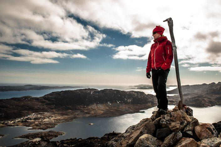 A hiker standing on a viewpoint high over Qaqortoq in South Greenland. Photo by Camilla Hylleberg